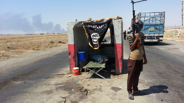 An ISIS militant stands guard at a checkpoint captured from the Iraqi Army outside Beiji refinery on June 19, 2014.