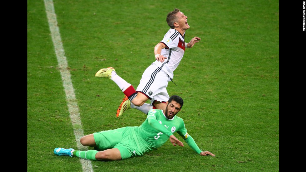 Algerian defender Rafik Halliche slides under Germany's Bastian Schweinsteiger. Halliche received a yellow card for the challenge.