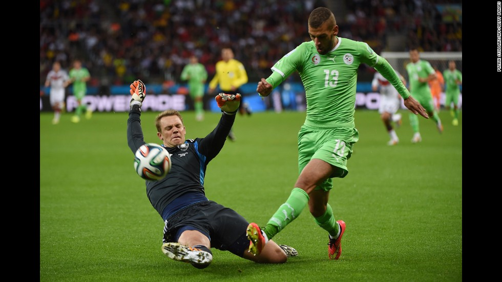 German goalkeeper Manuel Neuer, left, tackles the ball away from Algerian forward Islam Slimani.