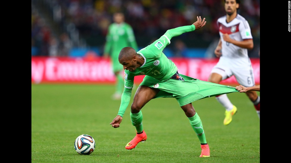 Yacine Brahimi of Algeria has his shorts pulled by Philipp Lahm of Germany.