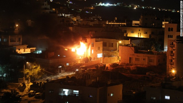 Flames and smoke billow from the blown-up house of Amer Abu Eisheh, one of two Palestinians suspected in the killing of three kidnapped Israelis, in the West Bank town of Hebron on July 1,2014. The Israeli army demolished the West Bank homes of two main suspects in the kidnap and killing of three young Israelis, witnesses told AFP. They said the houses of Marwan Qawasmeh and Amer Abu Eisheh, Hamas members in the city of Hebron, were blown up, in what a human rights group said was the first punitive demolition since Israel halted the practice in 2005. AFP PHOTO/ HAZEM BADER (Photo credit should read HAZEM BADER/AFP/Getty Images)