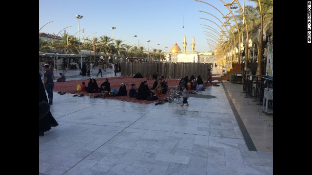 Shiite women and their children take a rest on a walkway between Imam al-Hussein and Imam al-Abass shrines.