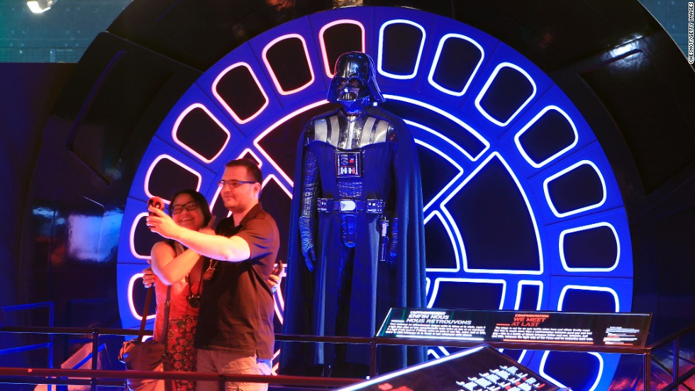 "Visitors take a selfie in front of a Darth Vader costume Thursday, June 26, at a ""Star Wars"" exhibition in Saint-Denis, France. The exhibition at the Cite du Cinema has more than 200 original pieces from the archives of Lucas Arts Museum, including models, props, costumes and sketches."