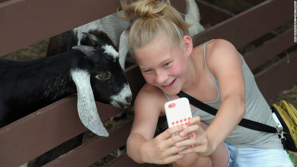 Anna Killo, 11, takes a selfie with a goat Monday, June 30, at the Kutztown Folk Festival in Kutztown, Pennsylvania.