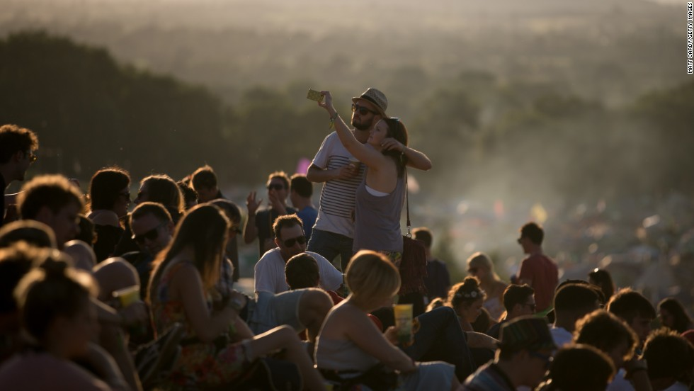 People in Pilton, England, gather to watch the sunset Wednesday, June 25, on the first day of the Glastonbury Festival, one of the largest music festivals in the world.