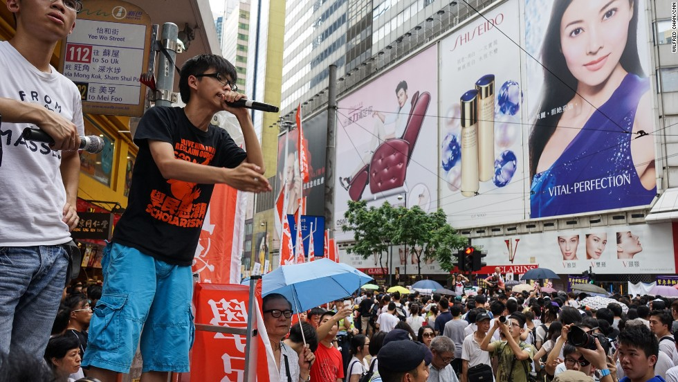 "During the march, Joshua Wong, 17, the founder of pro-democracy student group Scholarism, announced he would stage an illegal sit-in on the night of July 1. ""I may get arrested tonight. Will you all support me?"" he yelled to the crowd."
