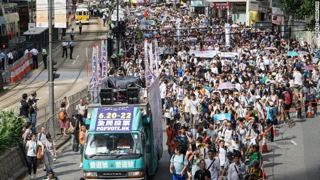 "A van bearing the logo of Hong Kong's unofficial referendum leads the procession out of Victoria Park on July 1. Nearly 800,000 people voted in the pro-democracy referendum, which Chinese state media called an ""illegal farce."""