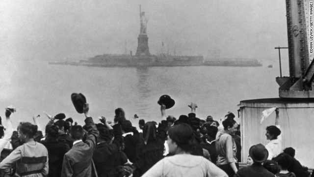 A group of immigrants traveling aboard a ship celebrate as they catch their first glimpse of the Statue of Liberty and Ellis Island in New York Harbor. (Photo by Edwin Levick/Getty Images)