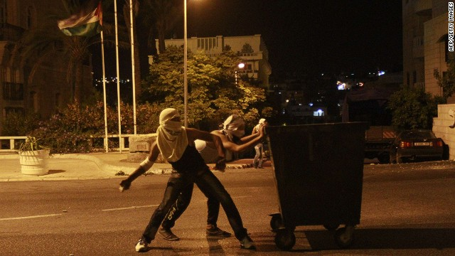 Palestinian protesters shield themselves behind a garbage container as they hurl stones toward an Israeli military observation tower at a section of the separation barrier to the main entrance of the West Bank city of Bethlehem after the abduction and killing of a Palestinian teen by suspected Jewish settlers, July 2, 2014. AFP PHOTO / MUSA AL SHAERMUSA AL-SHAER/AFP/Getty Images