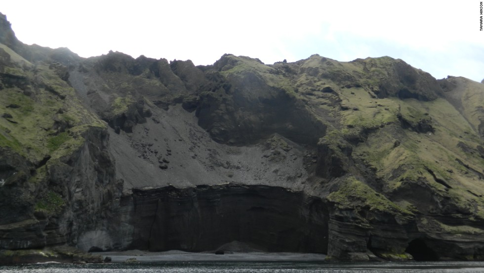 On boat rides around the Iceland's Heimaey Island, visitors pass towering banks of ash sloping down to the sea.