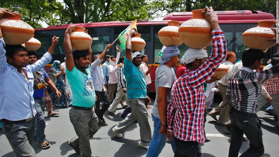 Activists carry pots on their heads June 13 during a protest march against power cuts and water problems in New Delhi.