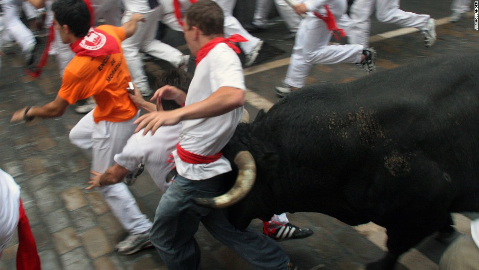 "A young man is caught between the bull's horns as he is tossed on July 8, 2007 in the old city streets of Pamplona. Thousands of ""runners"" test their skill, courage, and luck in the 900-meter course made famous by Ernest Hemingway's 1926 novel ""The Sun Also Rises,"" first published in 1926. The man was thrown against a fence but not injured. These images by photographer Jim Hollander appear in a new book ""<a href=""http://www.thebullsofpamplona.com"" target=""_blank"">Fiesta: How To Survive The Bulls Of Pamplona</a>."""