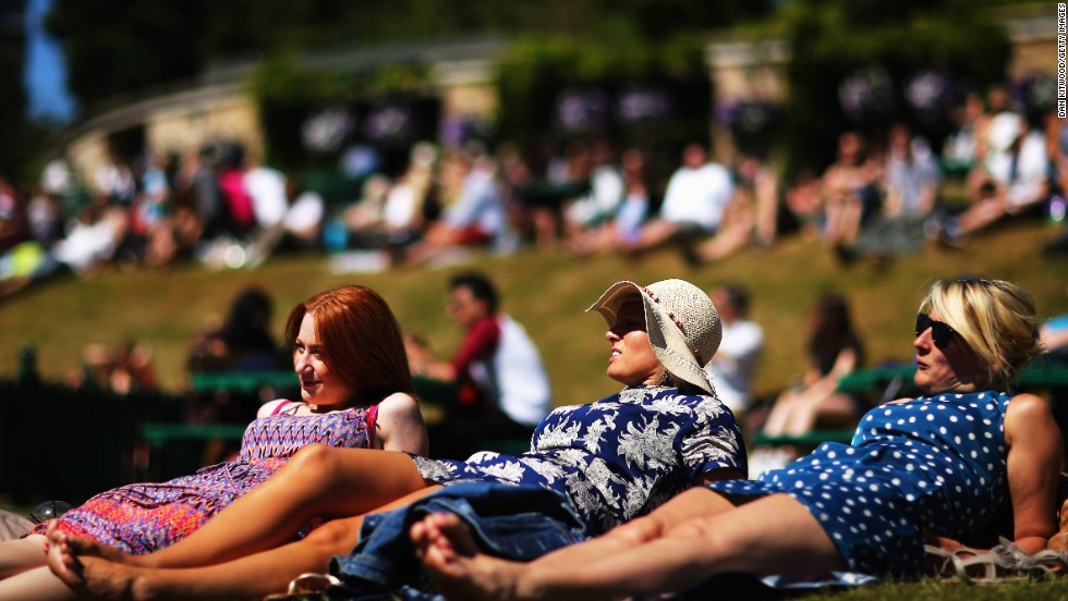 "Spectators soak up some sun on ""Murray Mound"" in the grounds of the All England Club."