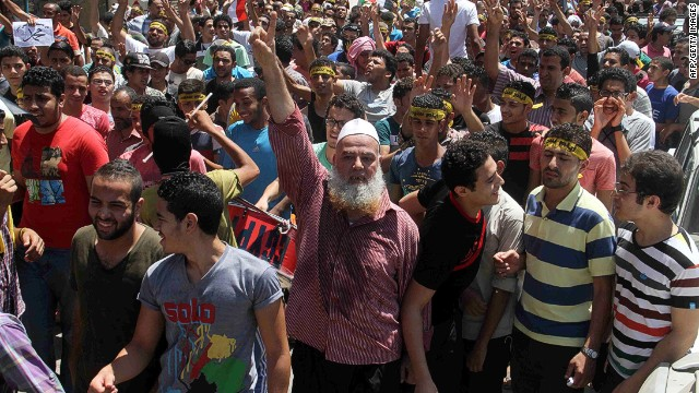 "Egyptian supporters of the Muslim Brotherhood movement shout slogans during a rally to mark the first anniversary of the military ouster of president Mohamed Morsi on July 3, 2014 in Cairo's Mattarya district. Egyptian police swiftly quashed Islamist protests firing tear gas and arresting dozens of demonstrators, as the protests are seen as a test of the Islamists' strength, with the Muslim Brotherhood-led Anti Coup Alliance having issued an aggressive rallying cry demanding a ""day of anger"" to mark Morsi's overthrow. AFP PHOTO / KHALED KAMEL"