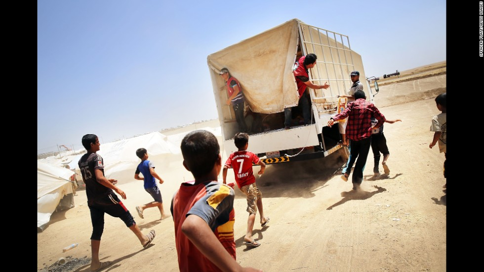 "Iraqis run behind a Red Crescent Society truck as it delivers food and other items to a displacement camp in Khazair, Iraq, on Monday, June 30. Many people <a href=""http://www.cnn.com/2014/06/13/world/gallery/iraq-under-siege/index.html"">have fled their homes</a> as vast swaths of northern Iraq, including the cities of Mosul and Tal Afar, have fallen to Islamist militants."