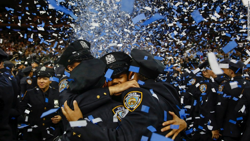 Members of the New York City Police Academy embrace during their graduation ceremony Monday, June 30.
