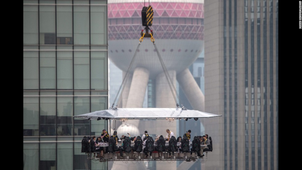 "People eat at a table lifted 50 meters (164 feet) above the ground in Shanghai, China, on Friday, June 27. The Dinner in the Sky restaurant, which is now in more than 40 countries according to <a href=""http://dinnerinthesky.com/"" target=""_blank"">its website</a>, was making its debut in China."