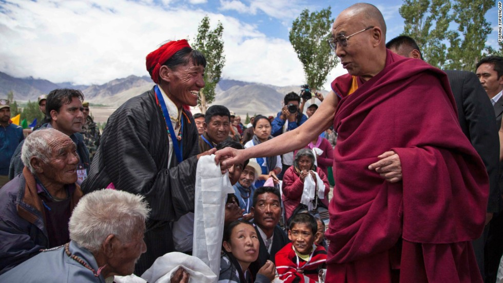 The Dalai Lama, right, talks to a Buddhist devotee as he arrives at a school near Leh, India, on Thursday, July 3.