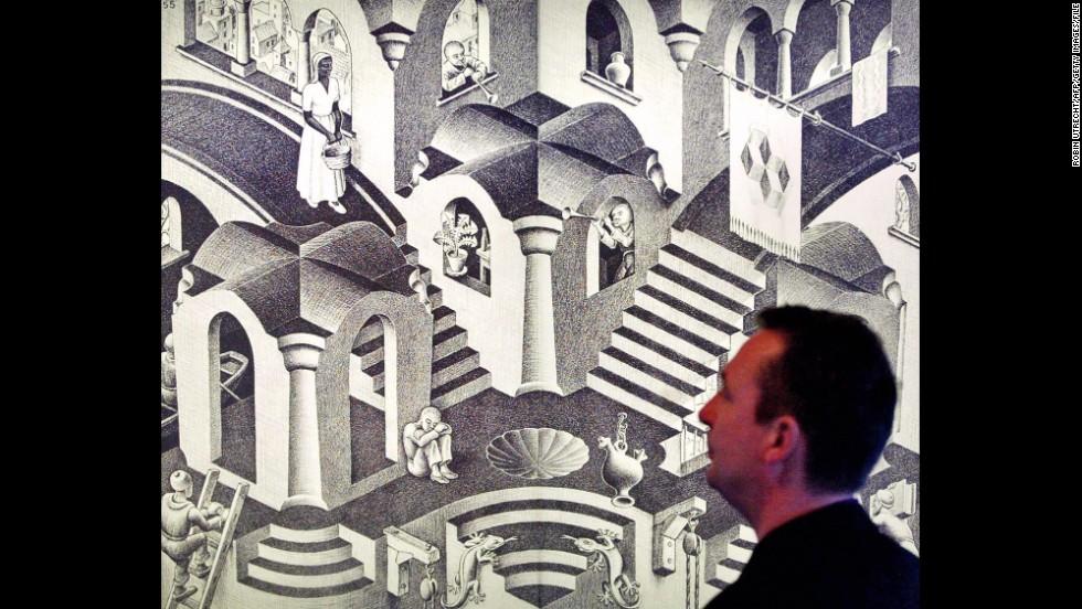 """A man looks at Dutch artist M.C. Escher's artwork """"Hol en Bol"""" (1955), displayed at the Escher Museum."""