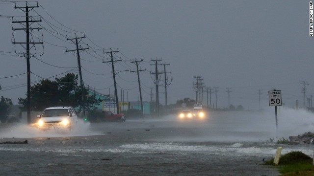 Vehicles navigate a flooded a highway as winds from Hurricane Arthur push water over the road in Nags Head, North Carolina, on Friday, July 4.