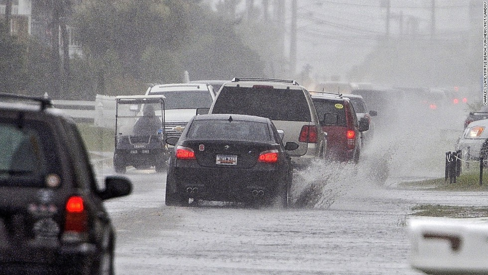 Traffic moves down a partially flooded road in Garden City Beach, South Carolina, on Thursday, July 3.