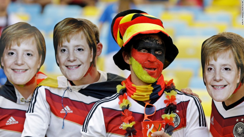 A Germany fan poses with friends wearing masks of German Chancellor Angela Merkel.