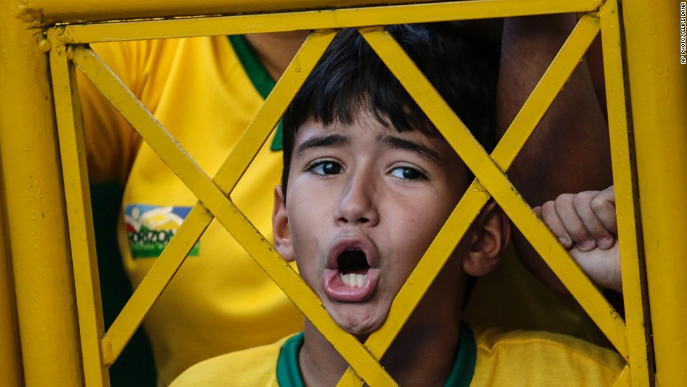 "JULY 4 - FORTALEZA, BRAZIL: A young soccer fan shouts from outside the stadium fence during the Brazil national football team's training session on July 3. The host nation will face Colombia today in a<a href=""http://cnn.com/2014/07/03/sport/football/world-cup-predictions/index.html""> World Cup quarterfinal match. </a>"