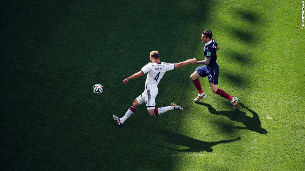 Germany's Benedikt Hoewedes, left, gets past Debuchy.