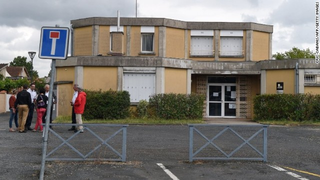 People gather in front of the Albi, France, school Friday after a kindergarten teacher was fatally stabbed in class.