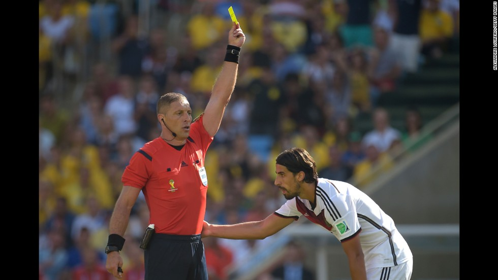 Referee Nestor Pitana shows a yellow card to Germany's Sami Khedira.