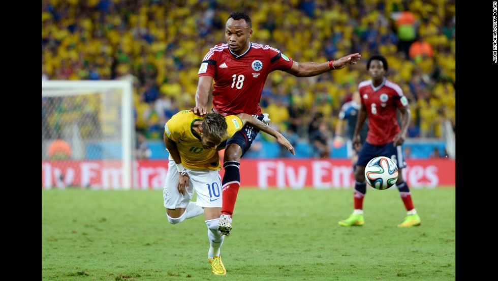 Neymar of Brazil is challenged by Juan Camilo Zuniga of Colombia.