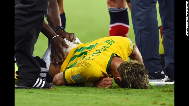 Neymar of Brazil receives treatment after a challenge during the 2014 FIFA World Cup Brazil Quarter Final match between Brazil and Colombia at Castelao on July 4, 2014 in Fortaleza, Brazil.