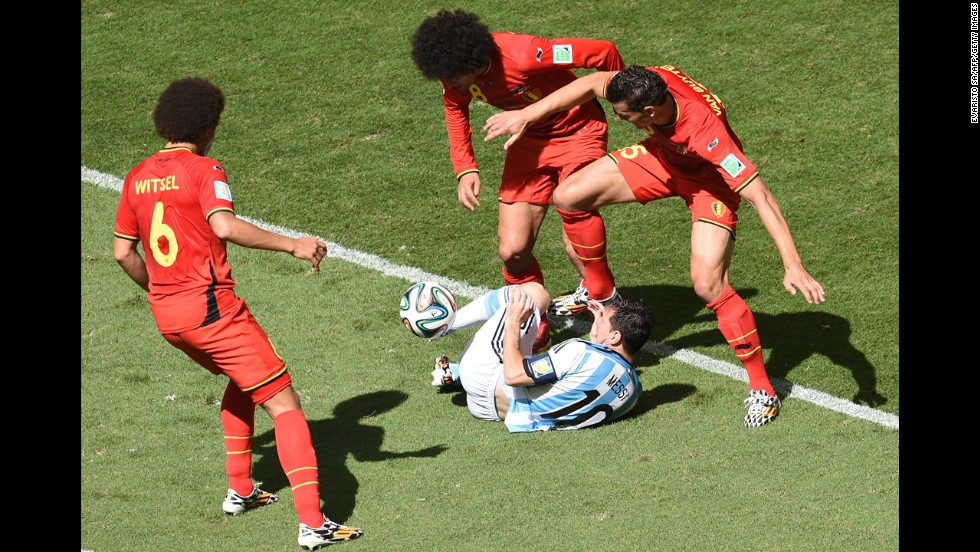 Messi falls amid Belgium players.
