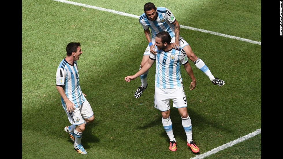 Argentina forward Gonzalo Higuain, right, celebrates with di Maria, top, and Messi, left, after scoring.