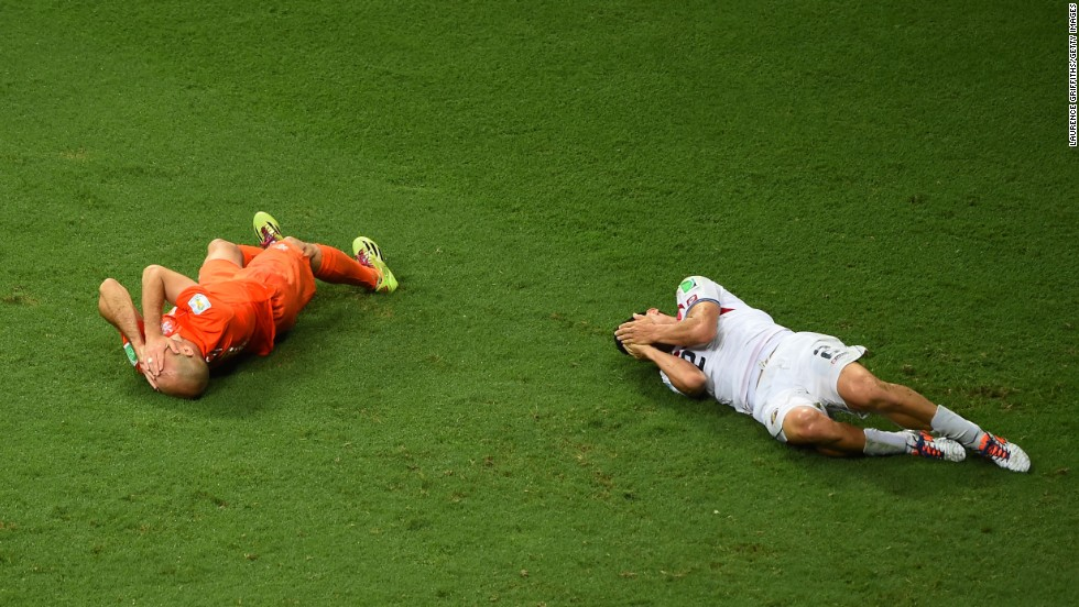 Arjen Robben of the Netherlands and Johnny Acosta of Costa Rica lie on the pitch after a collision.