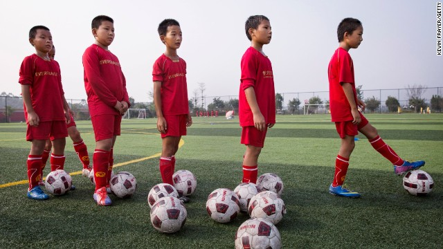 Young Chinese students wait for a kick during training at the Evergrande International Football School.
