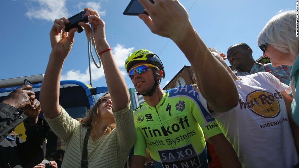 Two-time champion Alberto Contador takes a 'selfie' with some fans before the start of stage two. The 'selfie' fad is making a big impression on this year's Tour, although it has sparked safety fears among the riders.<br />
