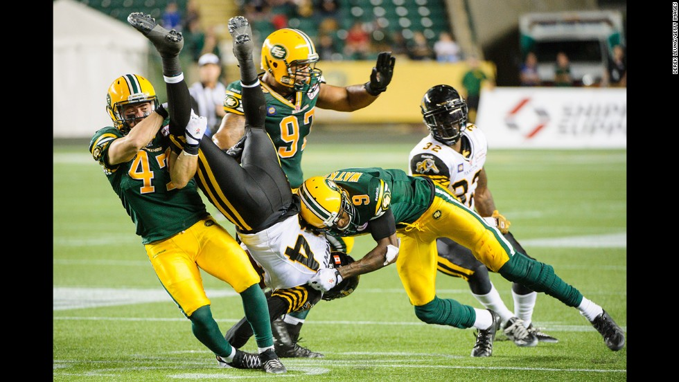 Bakari Grant of the Hamilton Tiger-Cats is flipped upside down as he is tackled by Edmonton Eskimos during a Canadian Football League game Friday, July 4, in Edmonton, Alberta.