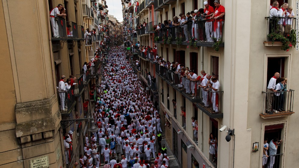 Revelers wait to run with the bulls along Calle Estafeta on July 7.