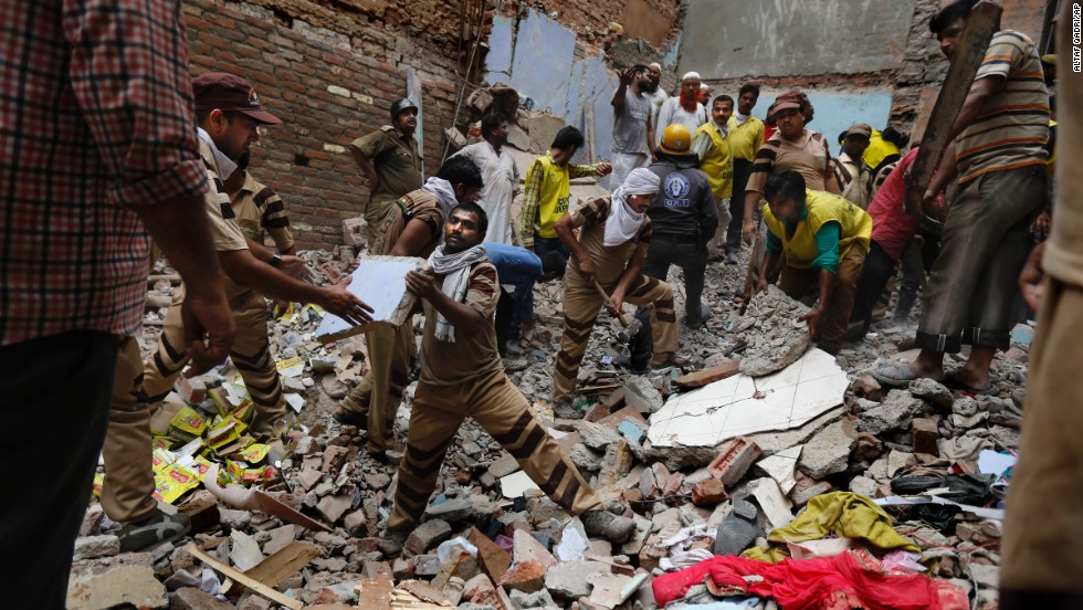 Rescue workers clear debris at the site of the building collapse on June 28.