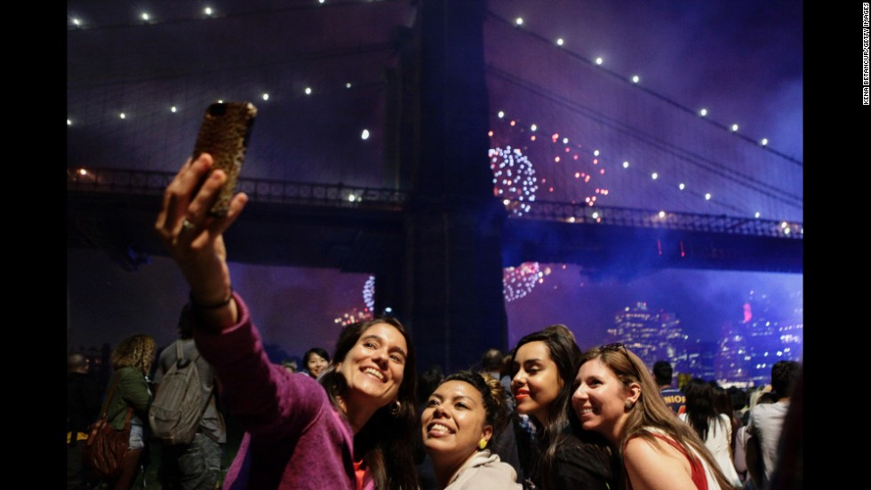 People pose for a photo Friday, July 4, as fireworks are seen near the Brooklyn Bridge in New York. The Fourth of July fireworks show returned to the East River for the first time since 2008.