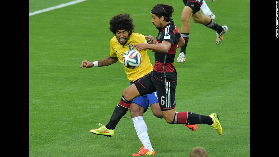 Brazilian defender Dante, left, fights off Germany's Sami Khedira.