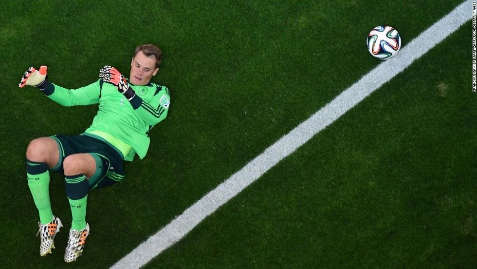 Neuer lies on the grass in the penalty box.