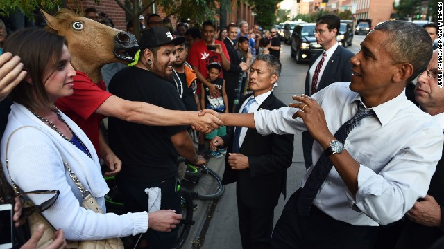 Obama shakes hands with a man wearing a horse-head mask on a street in Denver.