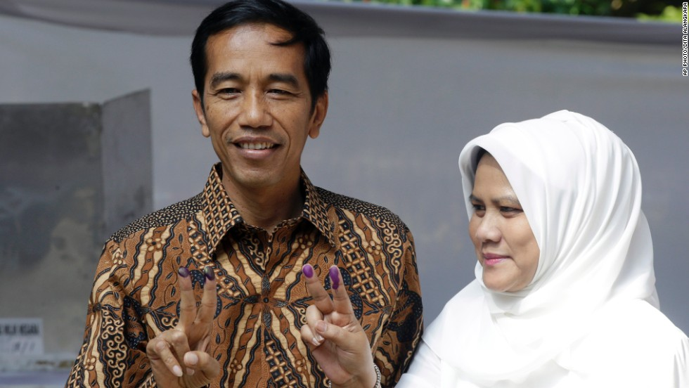 Indonesian presidential candidate Joko Widodo, at left, and his wife Iriana, show their inked fingers after casting their ballots during the presidential election in Jakarta on July 9.
