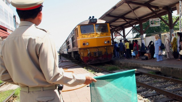 FILE PHOTO: A railway guard gives the green signal to a train in Thailand's southern Yala province.
