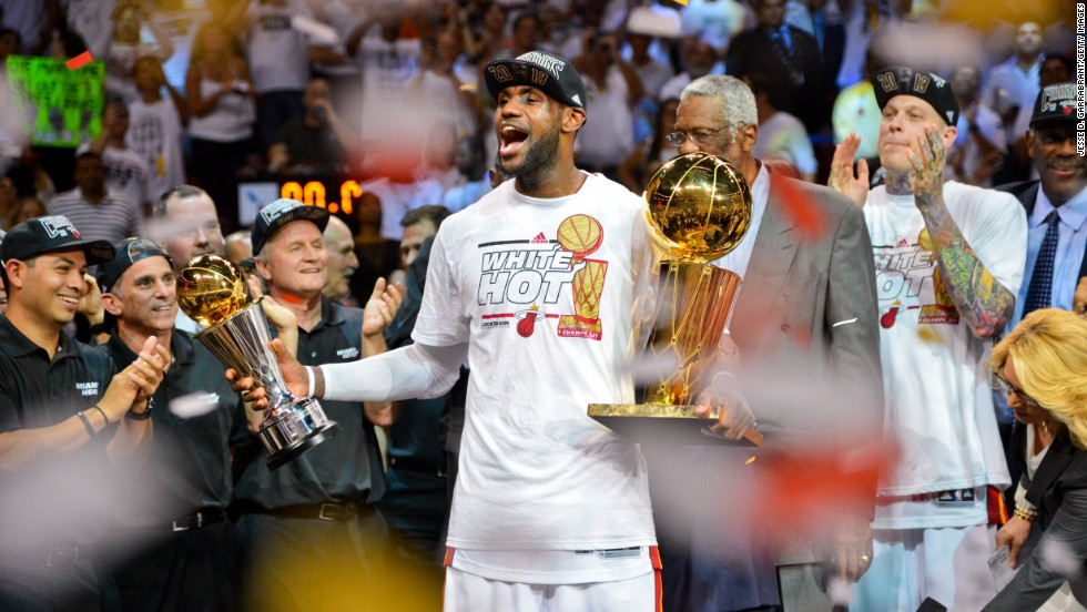 James holds the Finals MVP trophy and the Larry O'Brien Championship trophy after the Heat defeated the San Antonio Spurs to win back-to-back titles in June 2013.