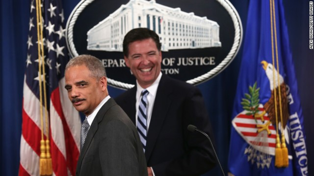 Attorney General Eric Holder (L) and FBI Director James Comey (R) leave after a major law enforcement action announcement at the Justice Department June 30, 2014 in Washington.