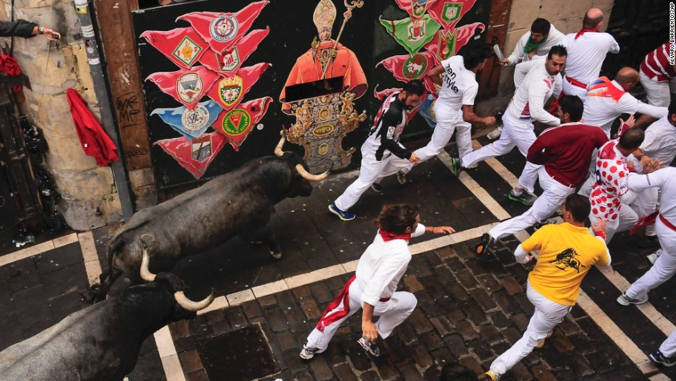 Runners pass a wall painted with an image of San Fermin, the saint the festival is named for, on July 13.