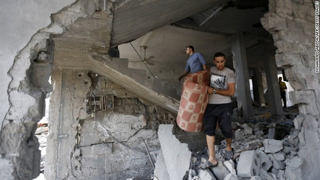 Palestinians inspect the rubble of their building that was partially destroyed following an Israeli airstrike in the morning on July 13, 2014 in Gaza City.